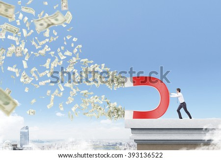 Businessman on roof with magnet pulling dollars. City and sky at background. Concept of attracting money. - stock photo
