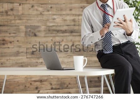 Businessman on tablet pc - stock photo
