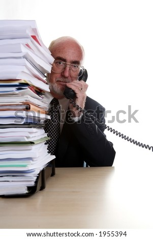 Businessman on telephone with pile of paperwork