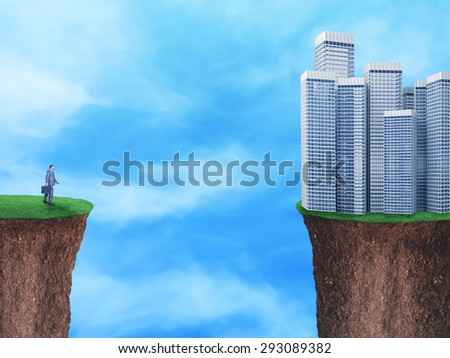 Businessman on the edge looks at downtown - stock photo