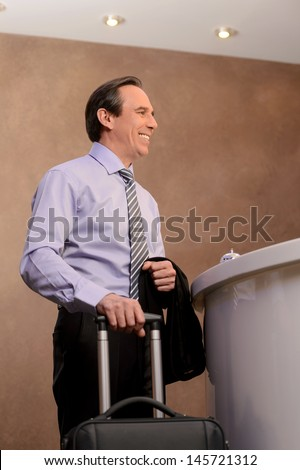Businessman on the hotel reception. Cheerful mature businessman standing near the hotel reception and holding a suitcase in his hand - stock photo
