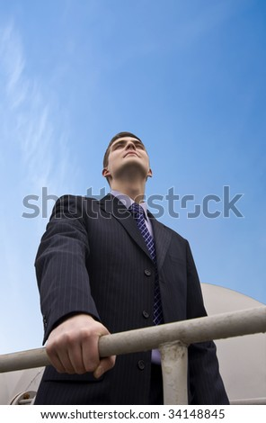 Businessman on the industrial background looking forward for the new acchivments