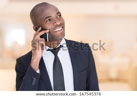 Businessman on the phone. Cheerful young African man in formalwear talking  on the mobile phone and smiling - stock photo