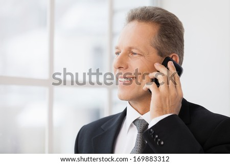 Businessman on the phone. Portrait of cheerful mature man in formalwear talking on the phone and smiling while standing near window  - stock photo