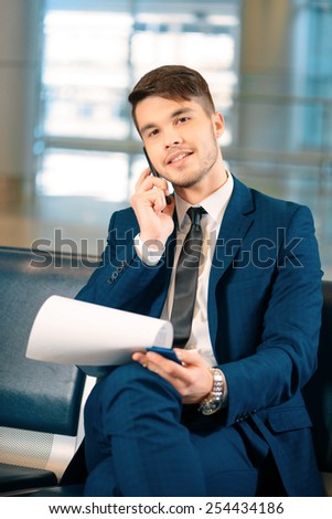 Businessman on the phone. Portrait of handsome smiling businessman in formalwear holding a clipboard and talking over the mobile phone while sitting in the airport  - stock photo