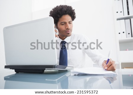 Businessman on the phone taking notes in the office
