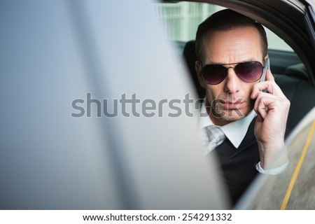 Businessman on the phone wearing sunglasses in his car - stock photo