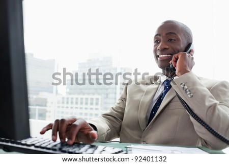 Businessman on the phone while using a computer in his office - stock photo