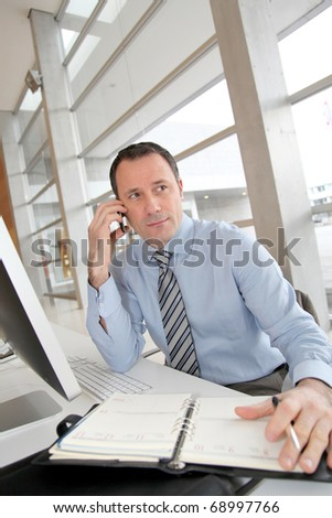 Businessman on the phone writing on agenda