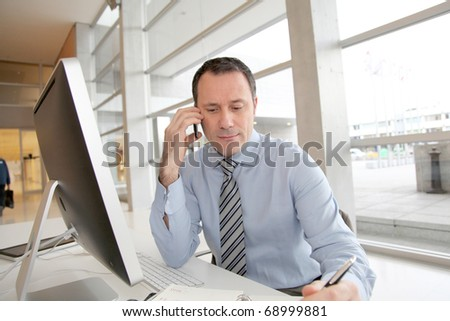 Businessman on the phone writing on agenda - stock photo