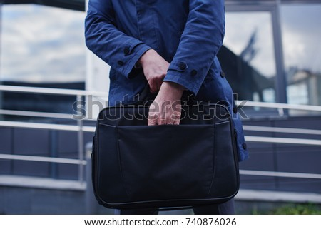 Businessman on the street puts his hand in the portfolio