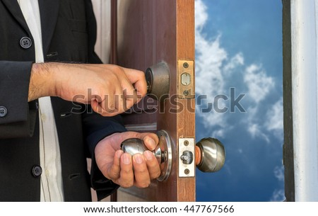 businessman open the door by key to blue sky and clouds - can use to display or montage on product or concept about travel - stock photo