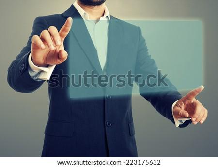 businessman opening virtual screen over dark background - stock photo