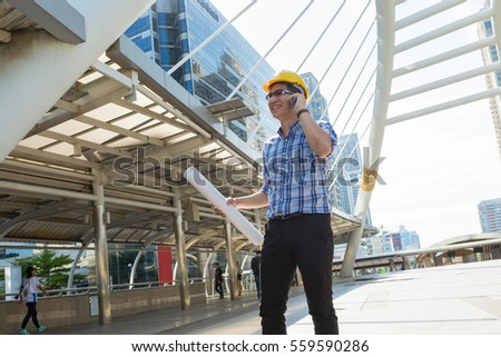 Businessman or Architect use Digital wireless Smartphone while walking to the Construction site as Industrial Technology Concept