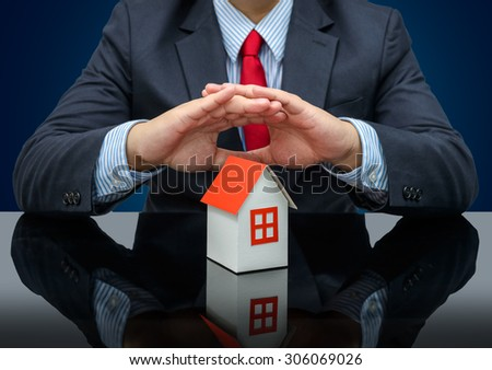 Businessman or estate agent and holding a model house and reflections - stock photo