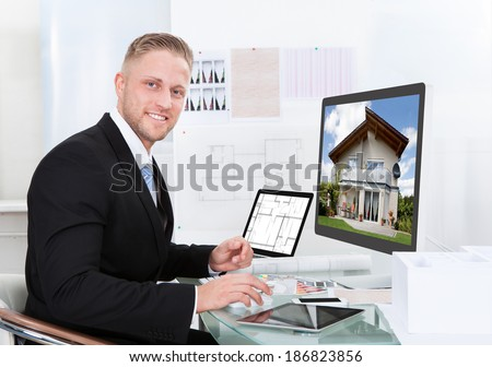 Businessman or estate agent checking a property portfolio online while sitting at his desk in the office looking at the exterior of a rural house visible on the desktop monitor - stock photo
