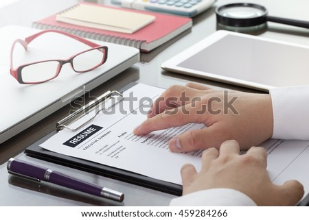 Businessman or HR Manager review a resume on his desk with Magnifier, computer laptop, digital tablet, calculator and glasses. Resume information with magnifier.