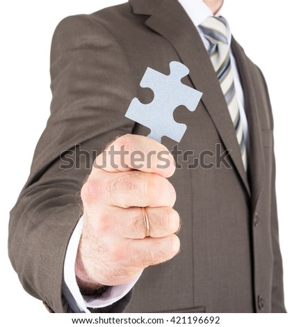 Businessman or innovator holding blank puzzle piece towards you isolated on white background