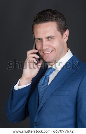 businessman or man smiling and talking on smartphone or mobile phone in violet suit and tie on grey background. Technology for business. Digital marketing, internet surfing and information