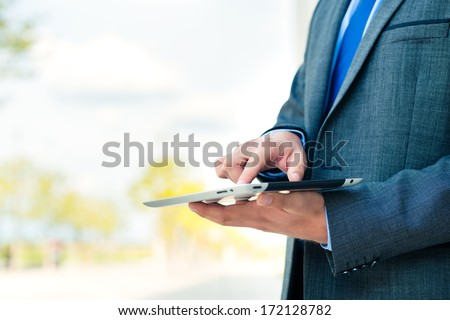 businessman or manager using pad or tablet computer reading or presenting on it - stock photo
