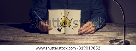 Businessman or student showing his working notebook with a hand drawn light bulb. Conceptual of innovation, idea and vision for personal and business progress. - stock photo