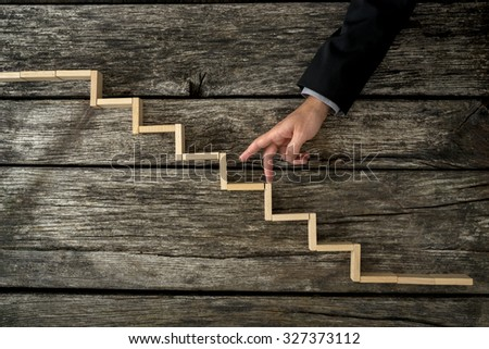 Businessman or student walking his fingers up wooden steps resembling a staircase mounted in rustic wooden boards in a conceptual image of personal and career development, success and aspiration. - stock photo