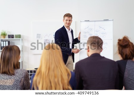 Businessman or team leader standing at a flip chart giving a presentation to an audience of his colleagues, view from behind their backs - stock photo