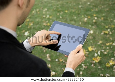 Businessman outdoors working with touch screen device. - stock photo