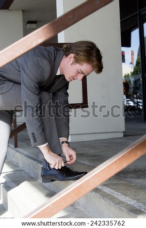 businessman outside at stairs ties his shoelaces