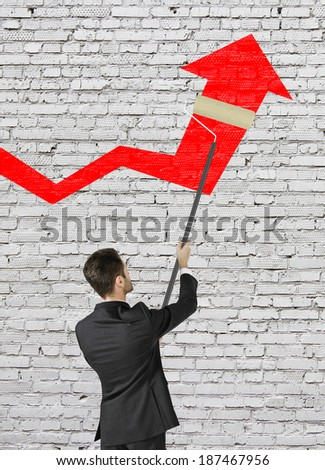 businessman painting big red arrow on brick wall - stock photo