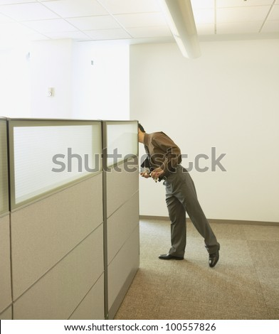 Businessman peeking around cubicle wall - stock photo