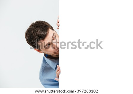 Businessman peeking from blank board isolated on a white background - stock photo