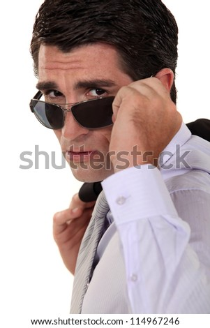 Businessman peering over his sunglasses - stock photo