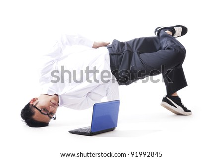 Businessman performing breakdancing with laptop - stock photo