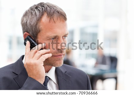 Businessman phoning in his office - stock photo