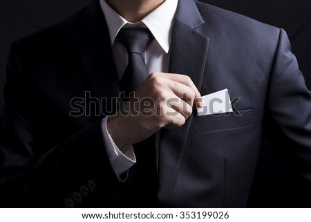 Businessman Pick Business Card: Isolated Black Background - stock photo