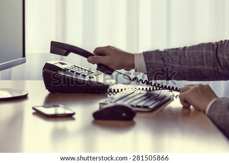 Businessman pick up or hangs up the phone in the office, keyboard, mouse, mobile, and monitor detail in the background, with vintage color tone effect.  - stock photo