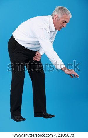 Businessman picking an imaginary something up