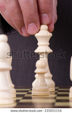 Businessman playing chess and holding queen chess piece. - stock photo