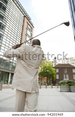Businessman playing golf in the middle of the financial district. - stock photo
