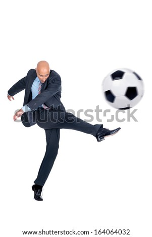 Businessman playing soccer ball isolated in white - stock photo