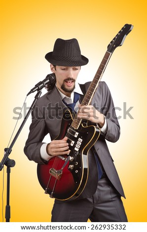 Businessman playing the guitar on white - stock photo
