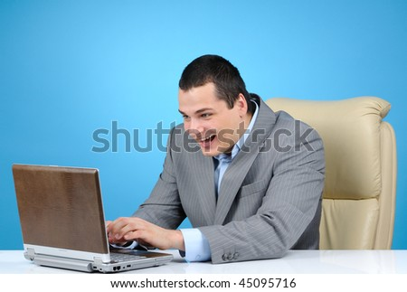 Businessman playing video game at  working hours on blue background