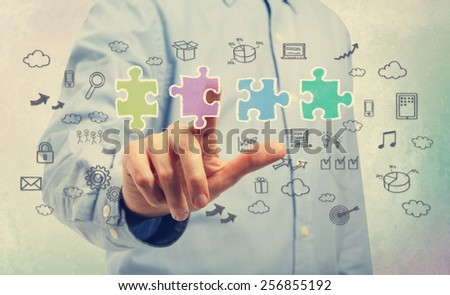 Businessman pointing at a piece of the puzzle with business ideas - stock photo