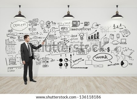 businessman pointing at business concept on wall - stock photo