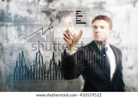 Businessman pointing at business graph on abstract concrete background - stock photo