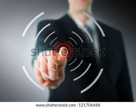 Businessman pointing at camera with digital elements - stock photo