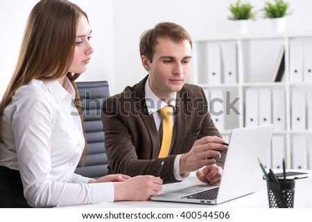 Businessman pointing at computer screen, businesswoman looking at it, office at background. Concept of cooperation.