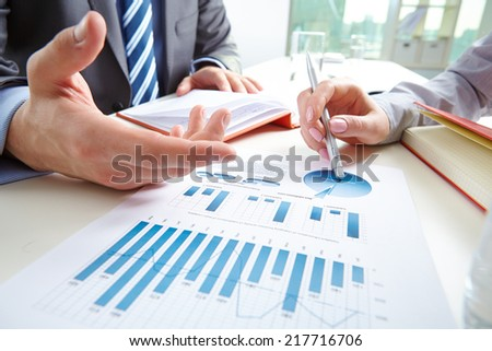 Businessman pointing at document while discussing it with colleague at meeting - stock photo