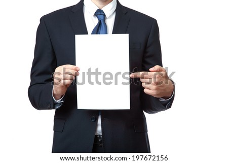 Businessman pointing at sign he is holding against a white background - stock photo